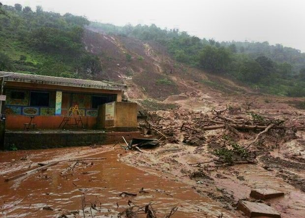 Deslizamento de terra é visto em vila no estado de Maharashtra, na Índia, nesta quarta-feira (30). Autoridades temem que 150 pessoas foram soterradas (Foto: AFP)