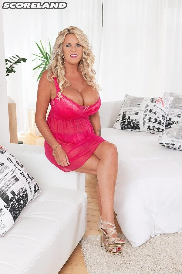 223cd1d724ff0 Fantastic blonde beauty with huge breasts in a tight cleavage revealing  dress.
