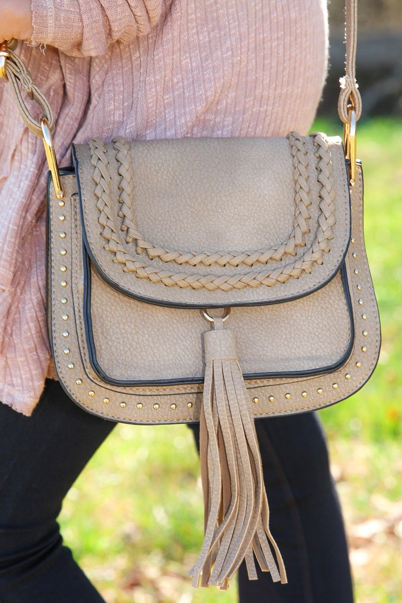 """Carrying this tasteful tote, you'll be looking as if you came back """"From The Badlands"""" with stylish enlightenment, with this bag as a momento. Luckily, achieving good style on the go isn't as difficult as a journey through the """"Badlands"""". It's merely a click away. Saddle bag features braiding and studded detail, a magnetic closure, and small zipper interior pocket. • 100% Polyurethane"""