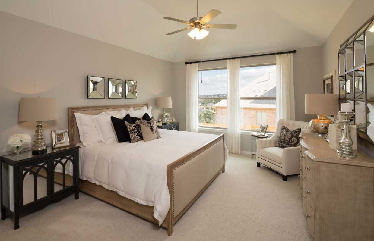 Sheer drapery, light wood furnishings and crisp white bedding make this master feel instantly calming, while mirrored decor adds a touch of personality. Belterra // Austin, TX // Highland Homes // Plan 204