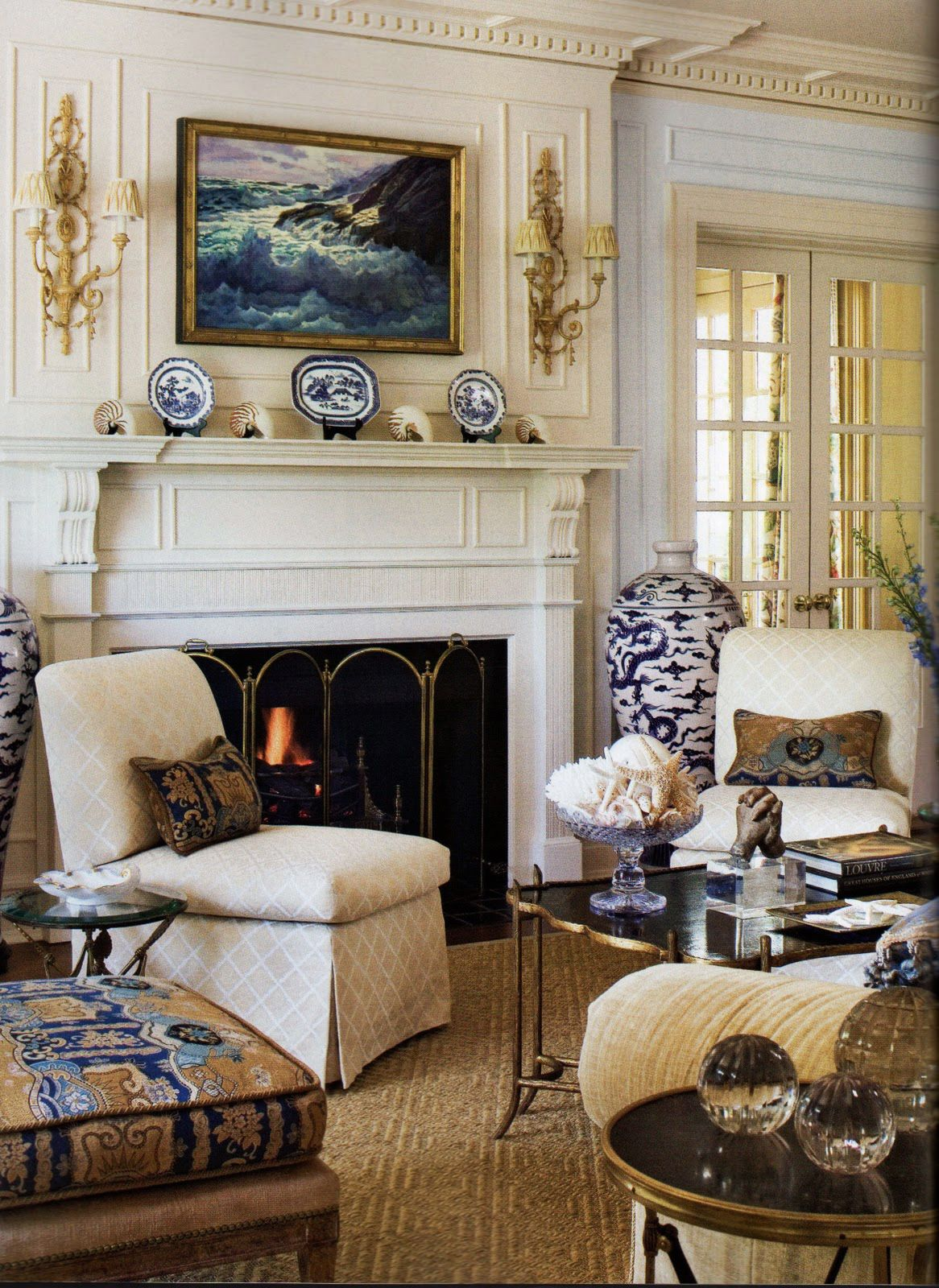 living room design with beautiful architectural details - dentil crown molding, wall panels, fireplace mantel, lovely Adam style sconces, decorated with blue accessories