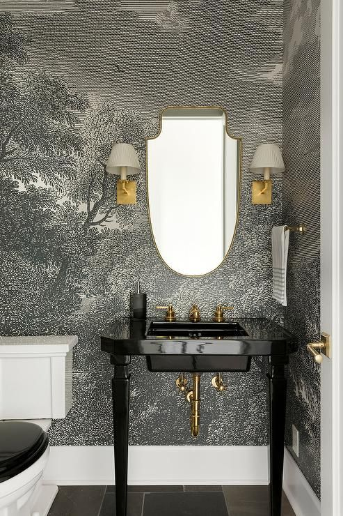 Photo of Dramatic gold and black powder room boasts a gold shield mirror hung from a blac…