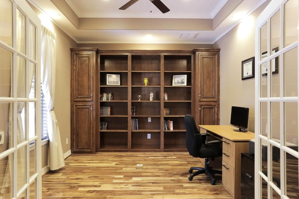 Study with trayed ceiling and recessed lighting for accent. Large, built in shelving for library display.