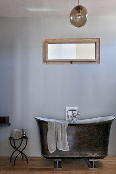 vieille baignoire noir, mur gris, fenêtre horizontale en bois ...