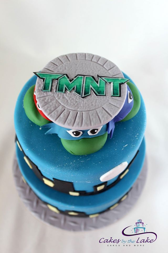 Tmnt Cake The Teenage Mutant Ninja Turtles Are Back This Two Tiered Cake Is Covered In Fondant With The Four Turtles Coming Ou Cake Tmnt Cake Fun Kids Party