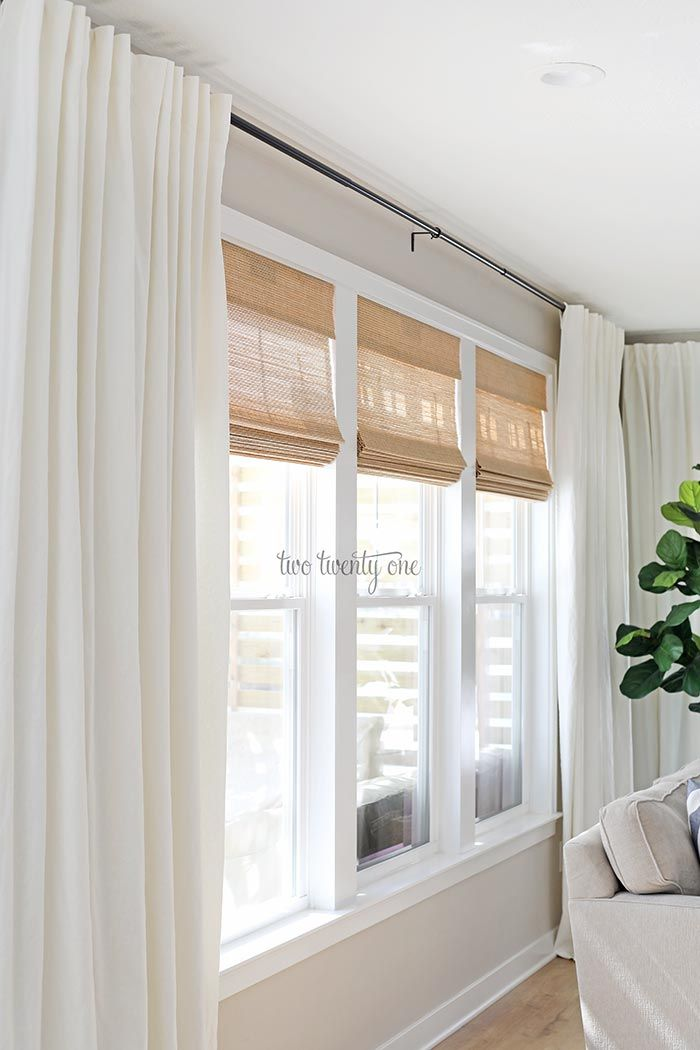Budget-friendly cordless woven shades and linen cotton curtains, paired with black curtain rods. Classic look for a living room on a budget! #livingroom #wovenshades #bambooshades #romanshades
