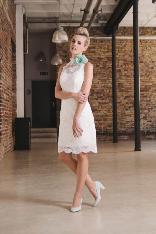 Kurzes Hochzeitskleid in schmaler Form aus feiner französischer Spitze. Dekolletee und Rücken sind zart mit Spitze bedeckt, die amerikanische Schulter und ein kleiner Stehkragen betonen vorteilhaft die figurbetonte Silhouette.