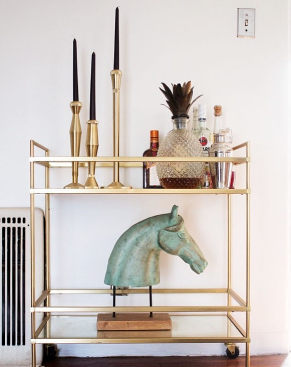The beautiful modern terrace bar cart black candles and a horse head statue are perfect accents