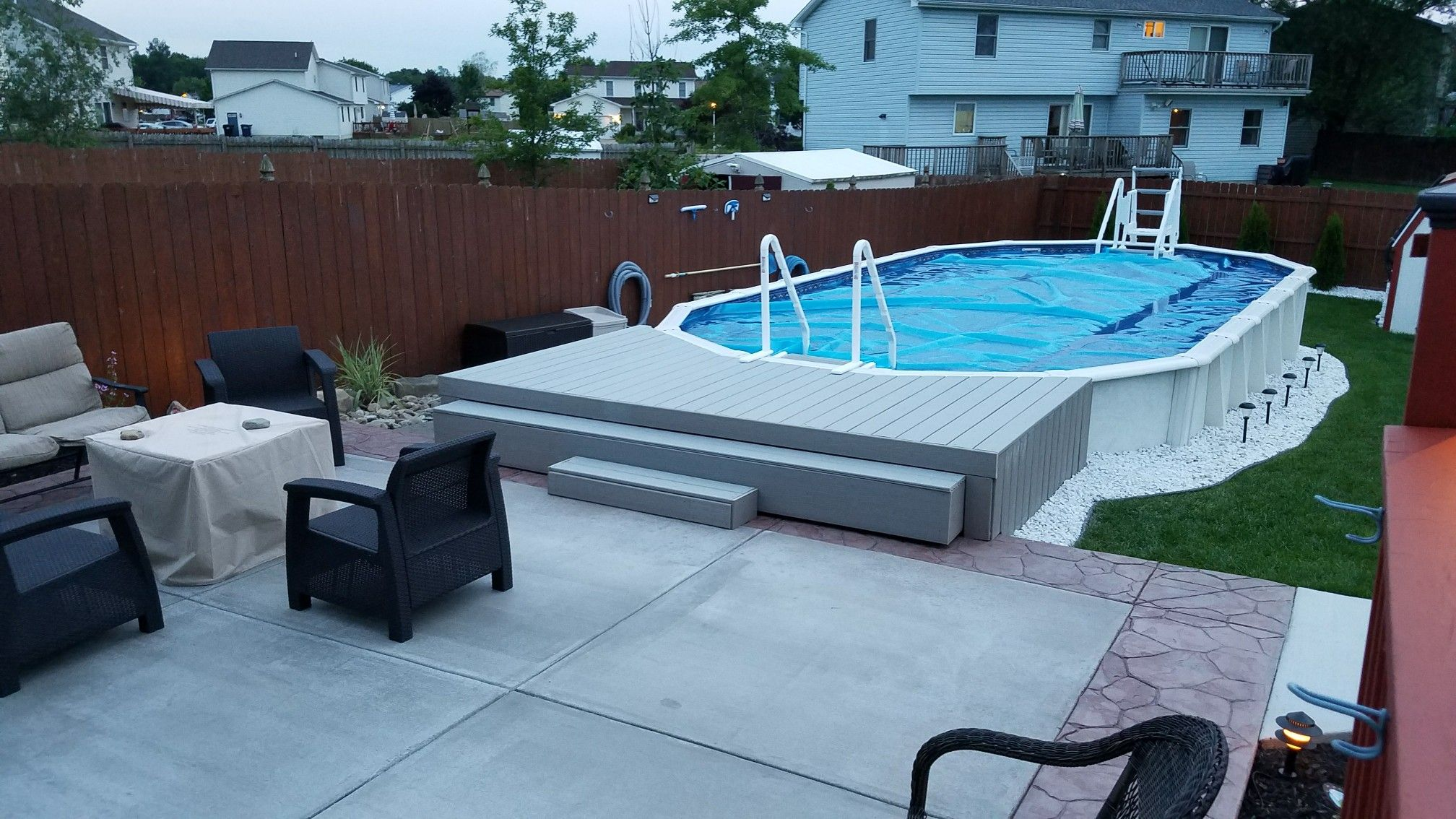 concrete patio and floating deck to semi recessed above ground pool