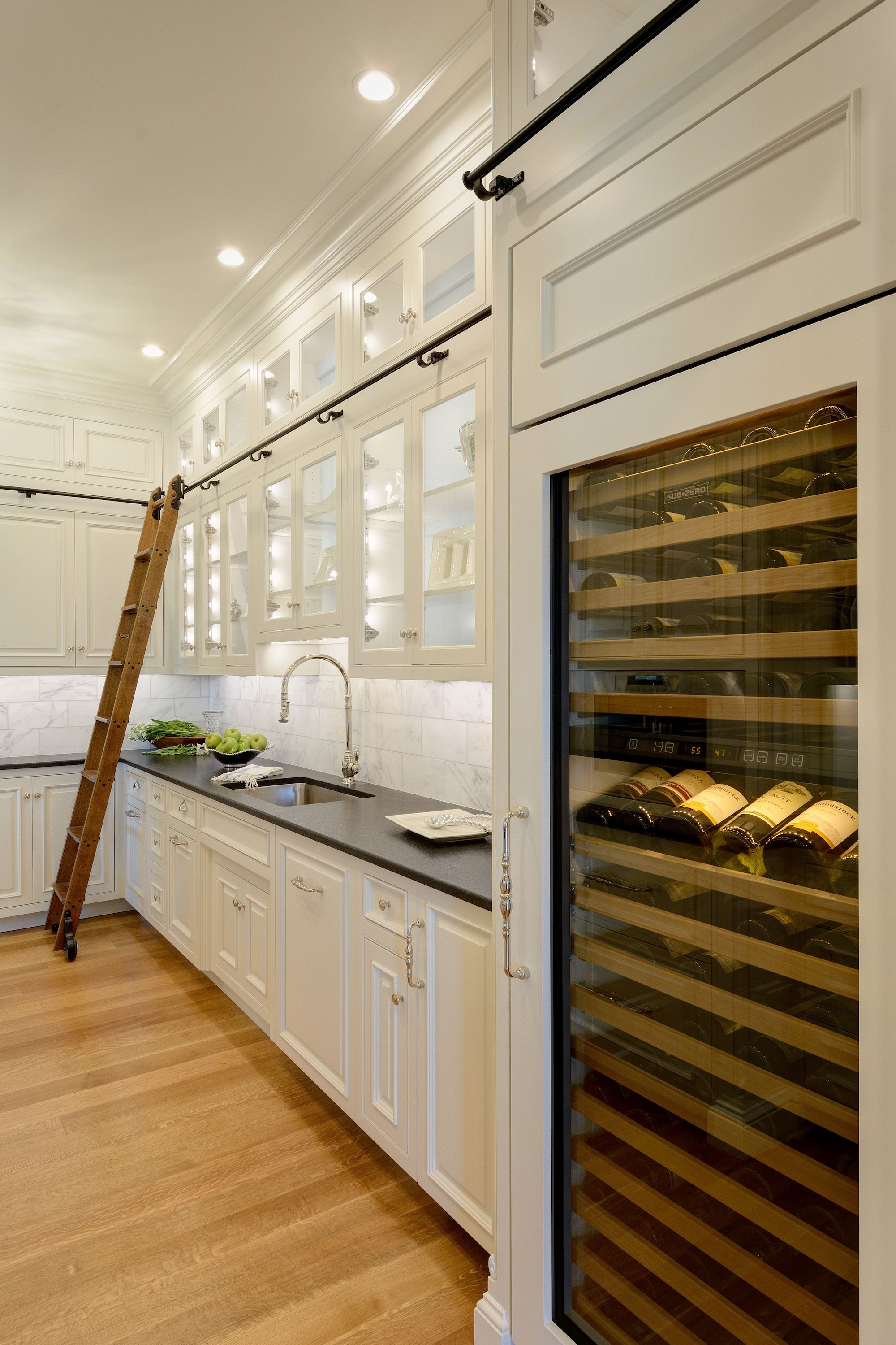 This large pantry area extends back from the wet bar and includes a full-size wine refrigerator and library ladder. #largepantryideas
