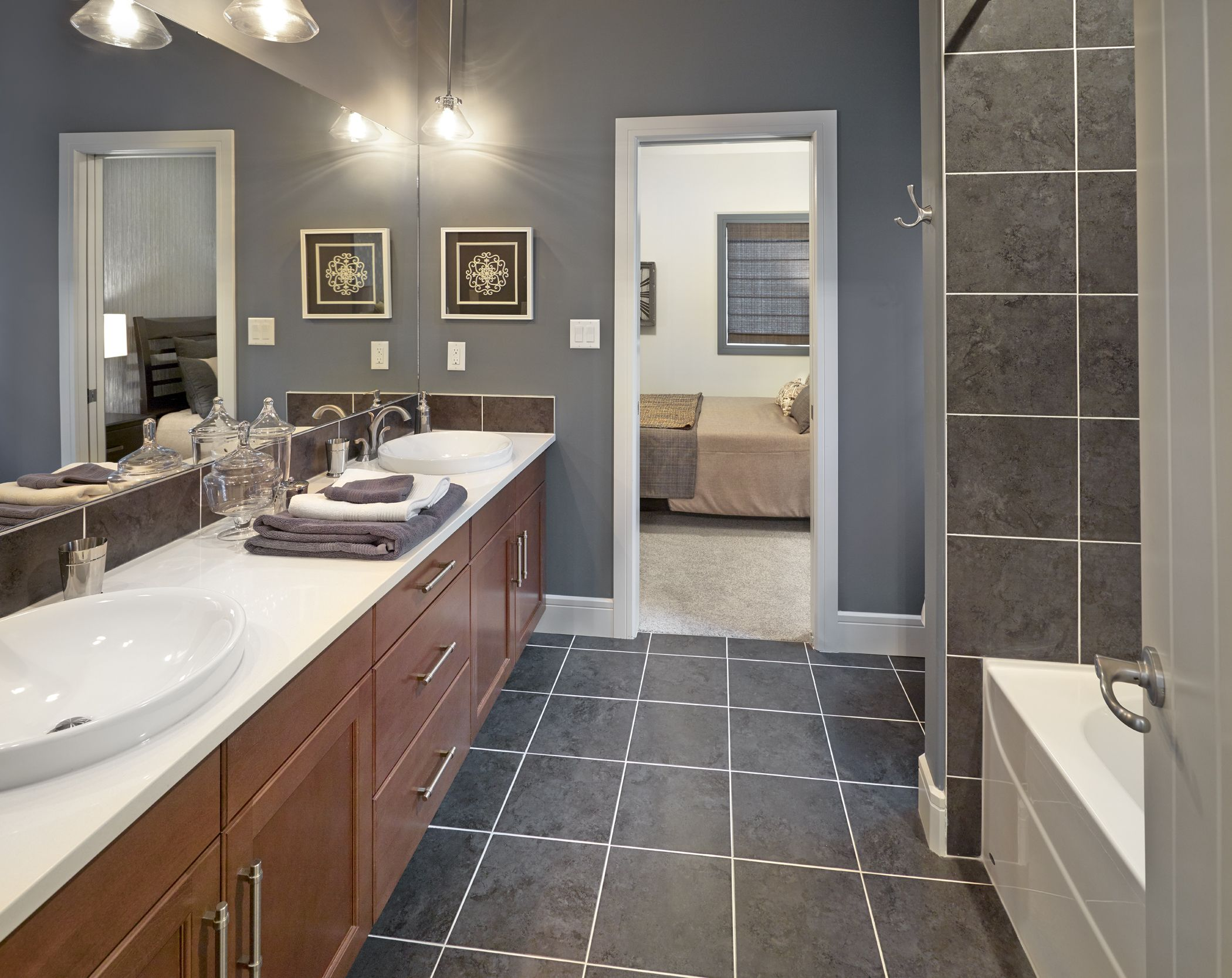 The Smoky Blue Grey Wall Color And Tile In This Ensuite Bath Plays Nicely With The Medium Wood Tones And Cris Grey Blue Bathroom Grey Bathrooms Grey Wall Color