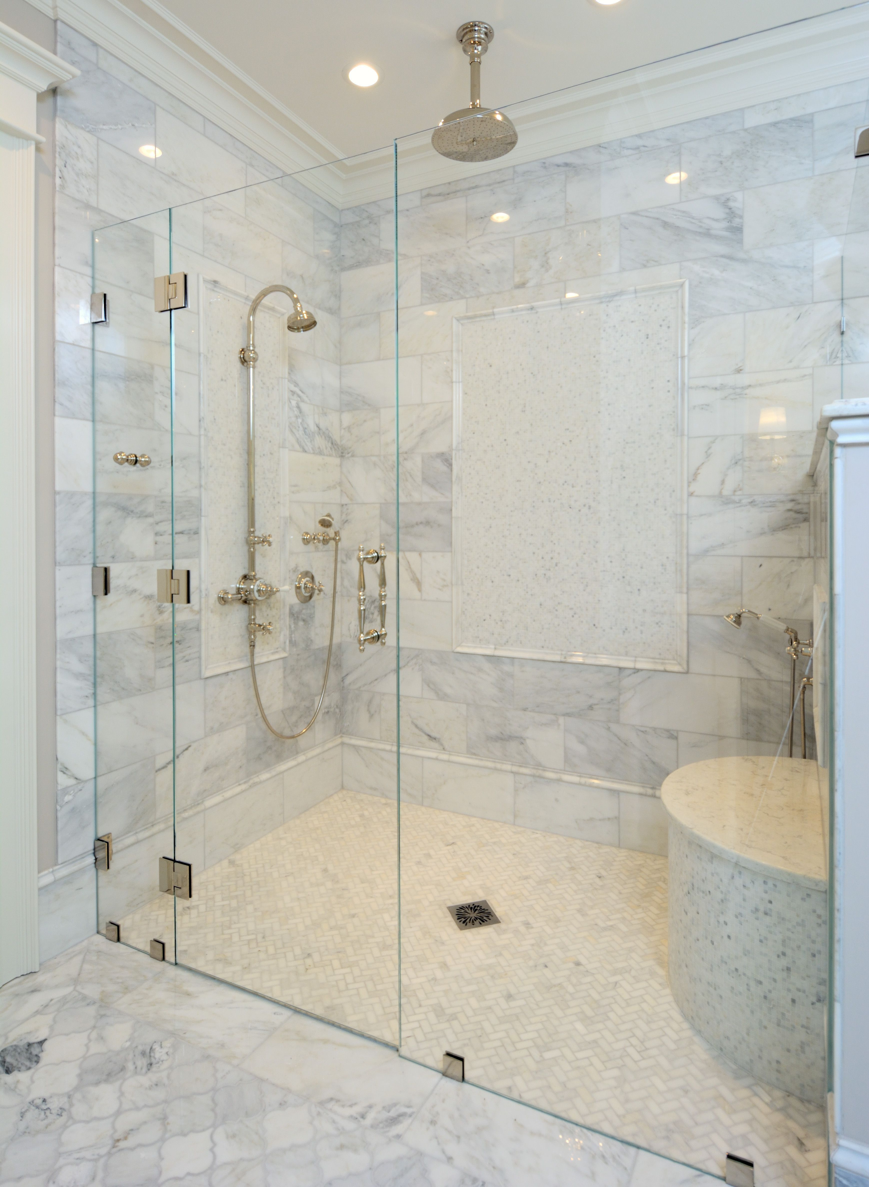A Large Walk In Glass Door Shower With Multiple Shower Heads And