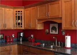 the black countertop goes well with the cabinets and red walls