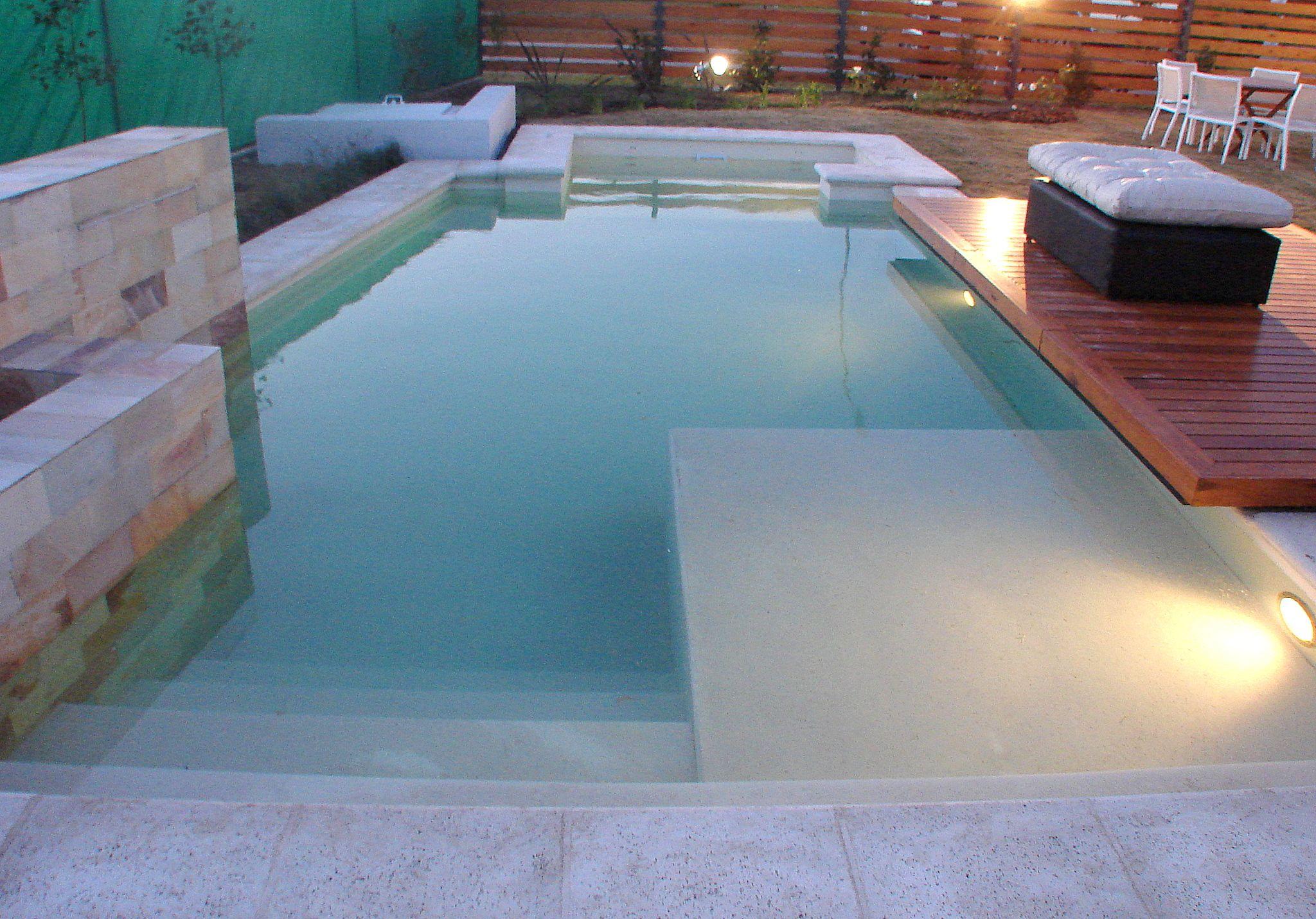 Piscina muro revestido en piedra deck de madera - Piedras para piscinas ...