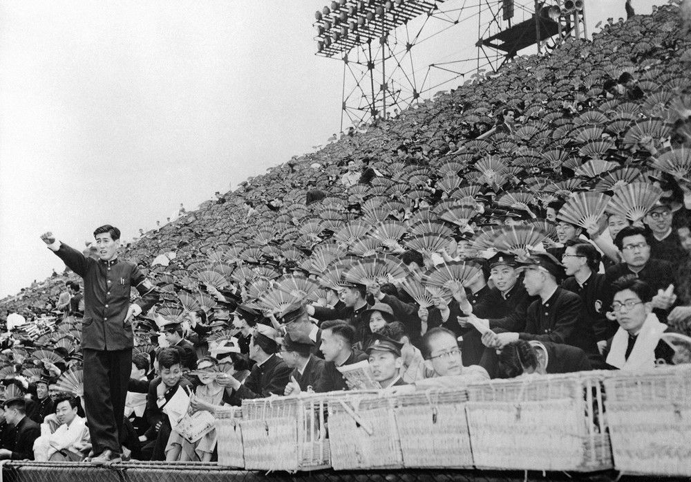Spectators equipped with fans watch a baseball game between Waseda and Keio Universities at Meiji Park, Tokyo, on June 1, 1954 by AP Photo