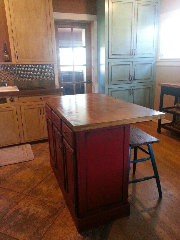 Red distressed island with  rustic bar stools