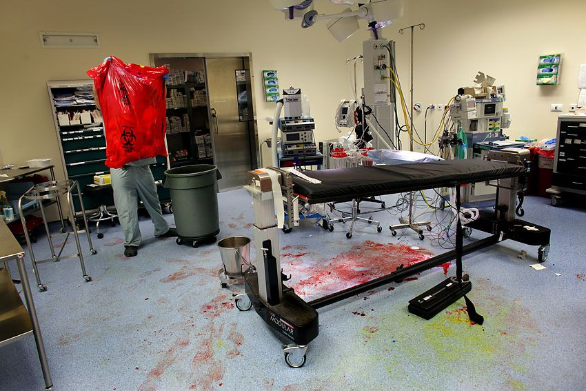A surgical technician cleans up after Army Cpl. Eddie Ward