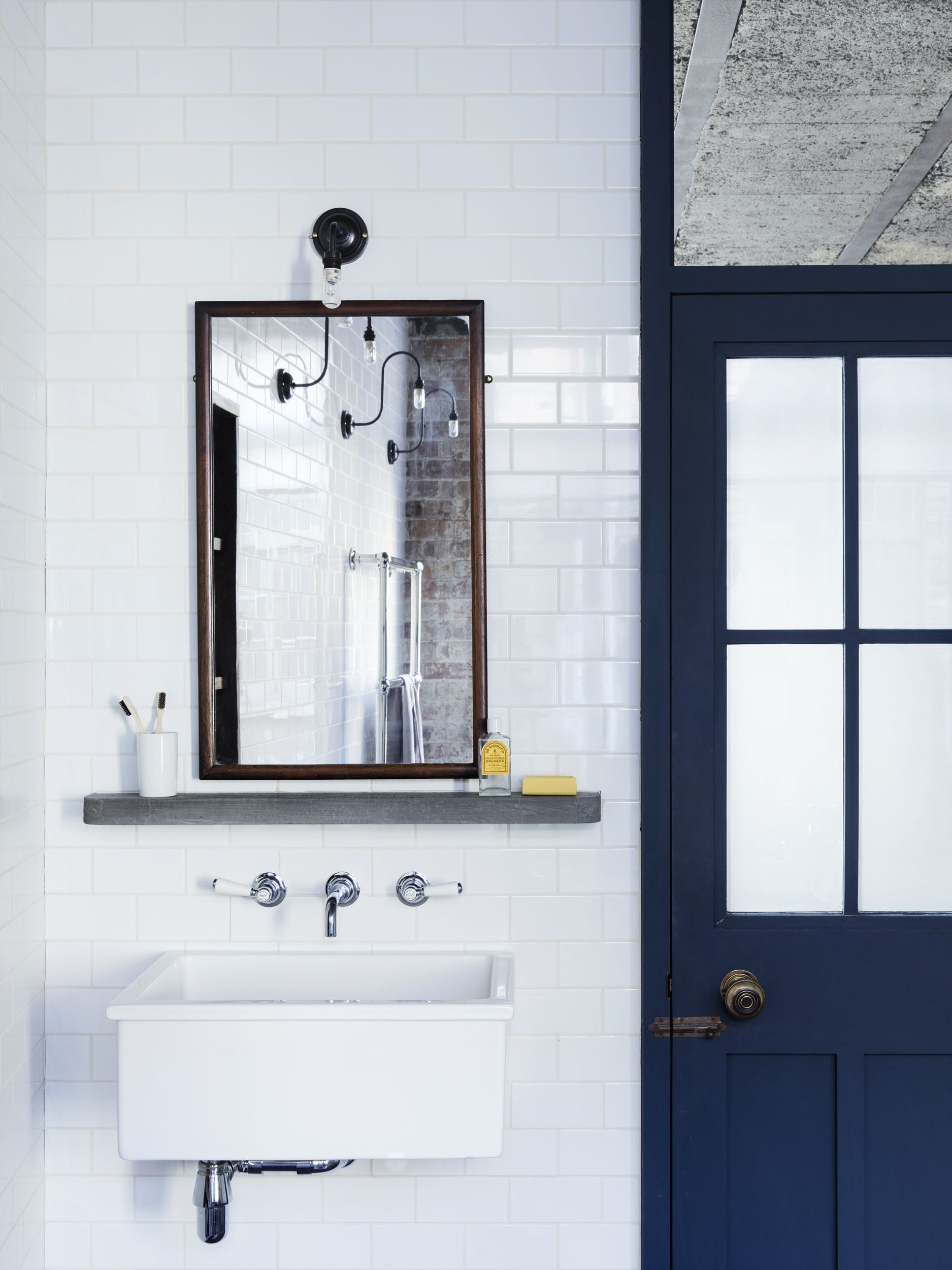 A cast concrete shelf sits below a vintage mahogany framed mirror - Hoxton  Square Renovation Project