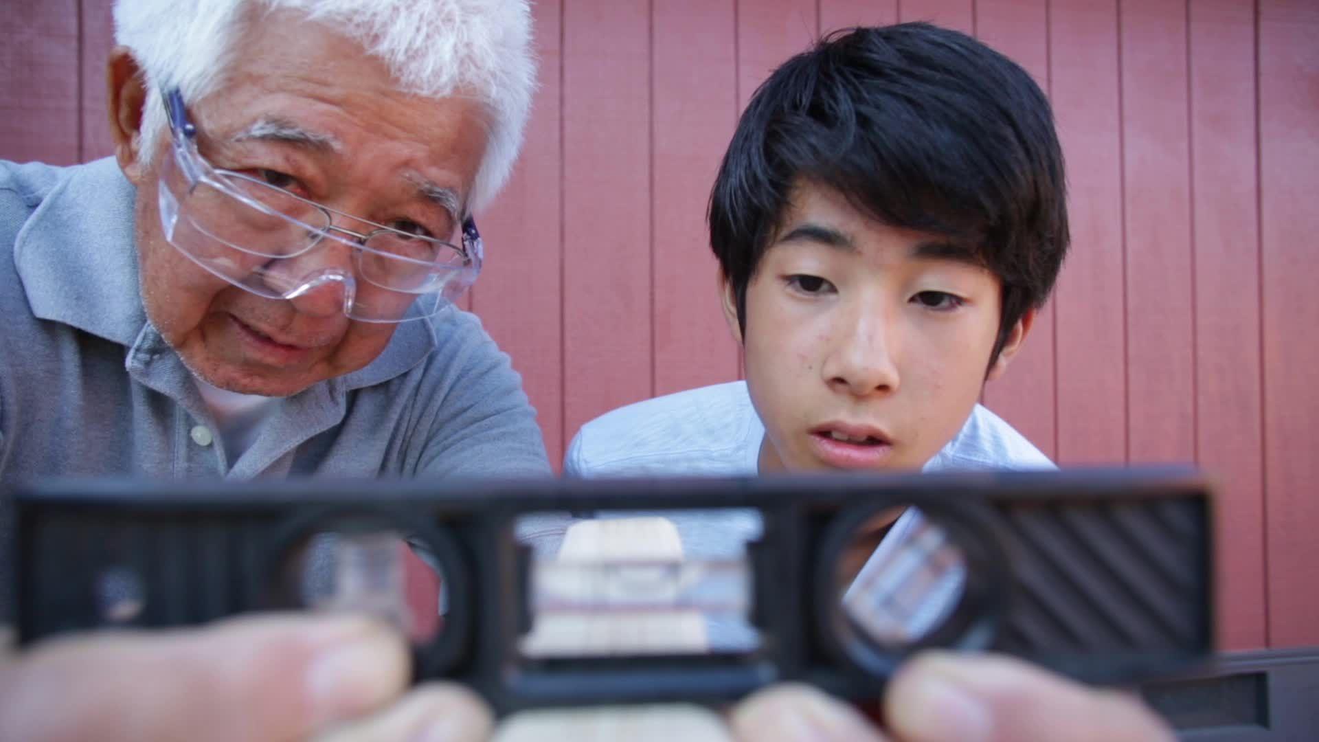 Asian Senior Man and Grandson Looking at Level Tool Stock Footage ManGrandsonSeniorAsian