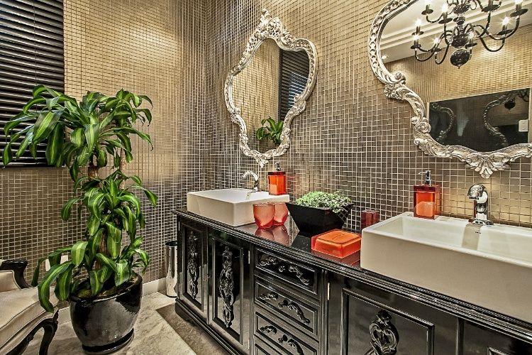 A arquiteta Daniela Cerbatto e a designer de interiores Cláudia Novak assinam o Banheiro Funcional, com 10m². Predominantemente bronze e preto, o ambiente leva pastilhas e elementos antigos na decoração. 19ª Casa Cor PR.