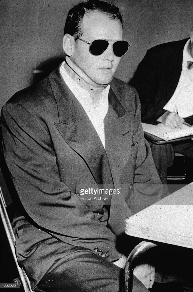 Dr  Samuel Sheppard sits at a courtroom table wearing a neck