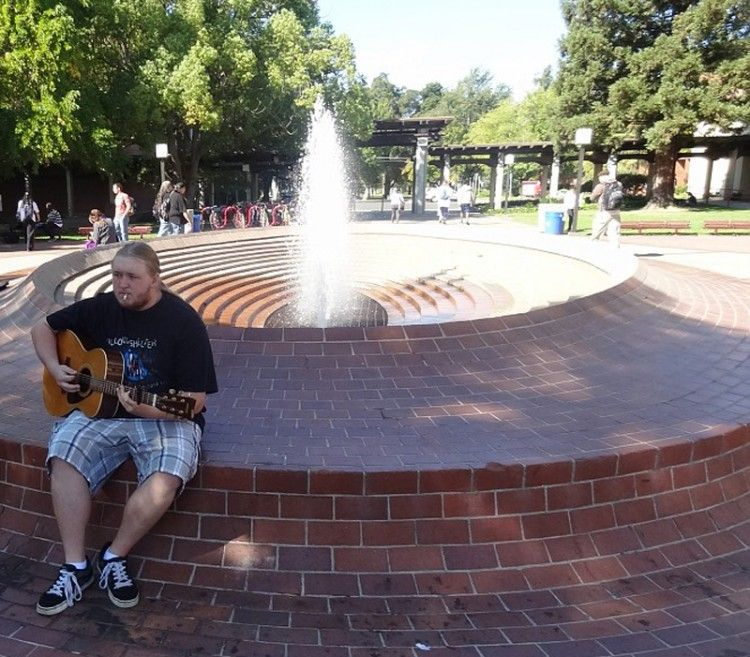 PICTURE OF THE DAY-Oct. 10, 2012. Erick Iverson 20 is a music philosophy major practicing his guitar on the fountain in the quad before class begins. Thomas Froberg | frobergtom@yahoo.com