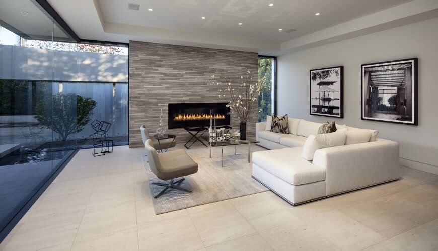 This Ultra Modern Family Room Pairs A White L Shaped Contemporary Sectional With Pair Of Grey Accent Chairs Around Minimalist Gl And Metal Coffee