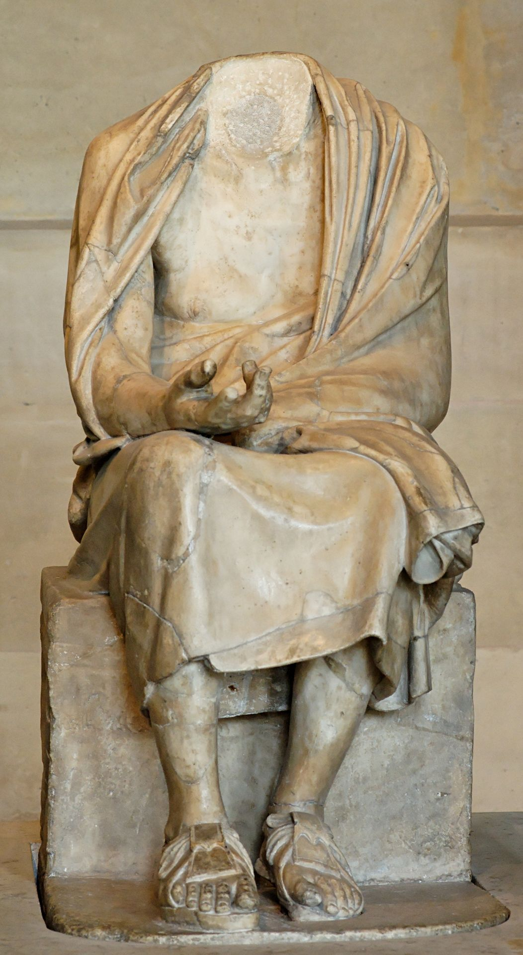 Seated old man. Marble, Roman copy of the 2nd century CE after a Hellenistic original, maybe the 3rd-century BC statue of Chrysippus by Euboulides described by Pliny (34.88). Courtesy & currently located at the Louvre, France.