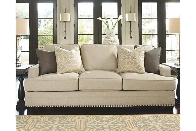 Beautiful tan couch with brown and tan throw pillows View 1
