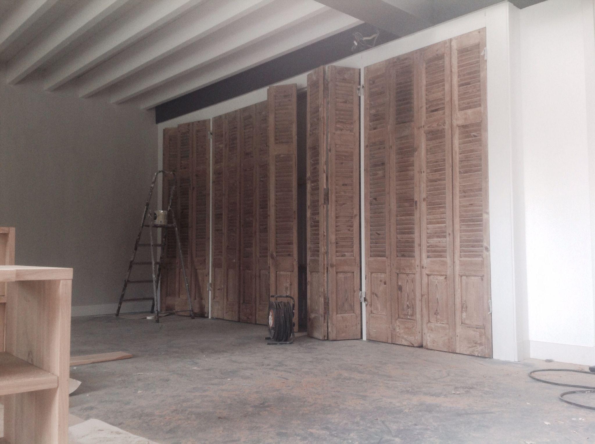 De kast in de woonkamer gemaakt met oude louvredeuren ingebouwd