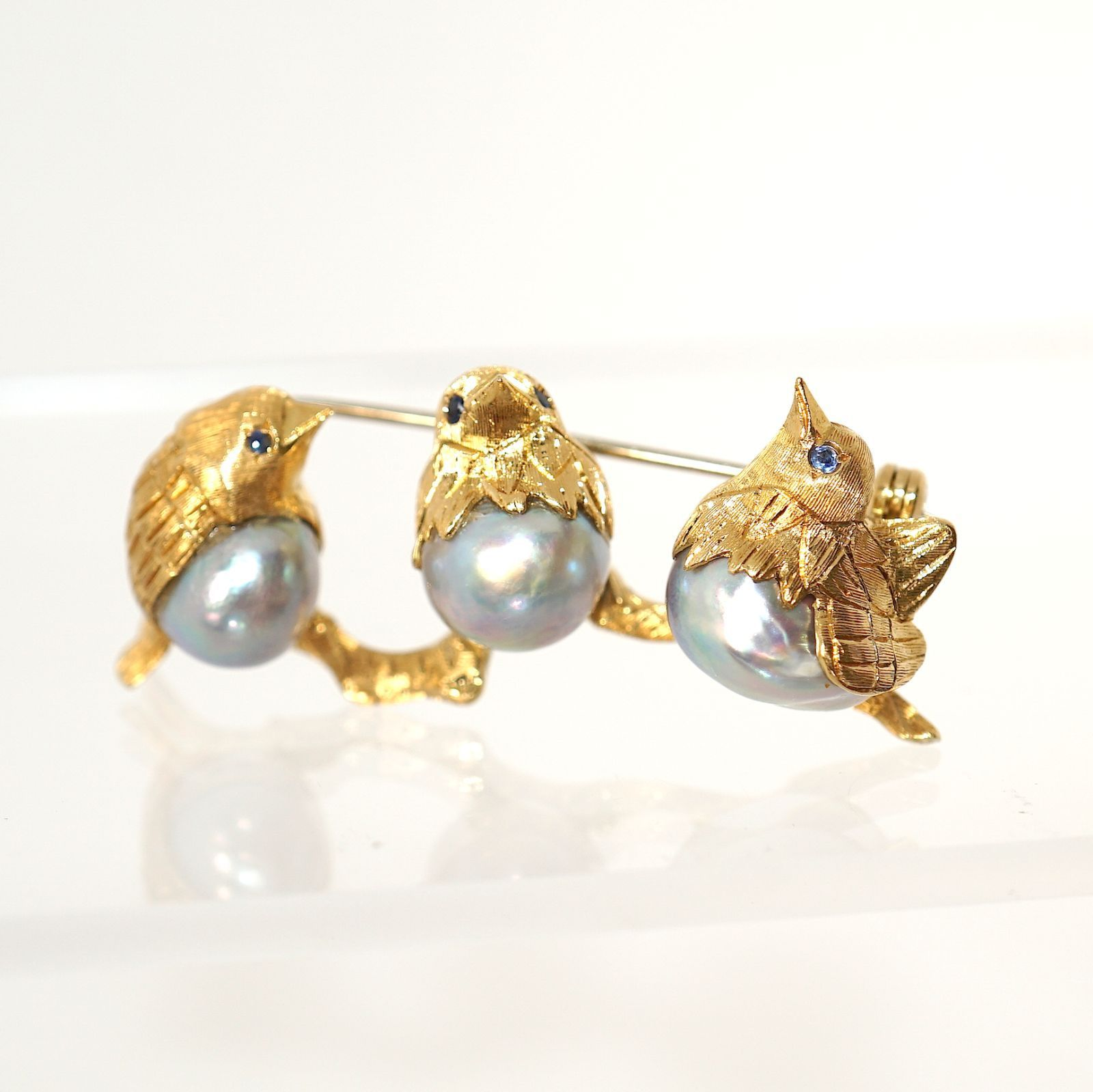 18K Gold Tahitian Silver Pearl Sapphire Singing Birds Brooch Fine Jewelry | eBay Three chirping bodies, 3 golden Italian birds on a branch as a brooch for your attention. Made of solid 18k yellow gold, with silver color Tahitian pearls as their body, and natural blue sapphire as eyes. Pearls are from left to right measured as 14mm, 11mm, 12mm. Brooch is 44mm wide. Will be coming with a certificate of authenticity and will be appraised for $3000.00. Buy-it-Now $1380