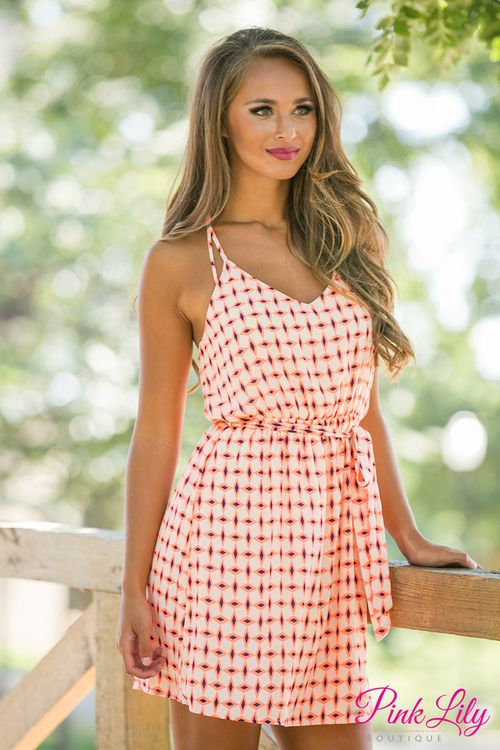 A pop of neon is always a good way to spice up an outfit! This dress has neon orange and navy print on an off white material with a detailed back that will be your favorite part!