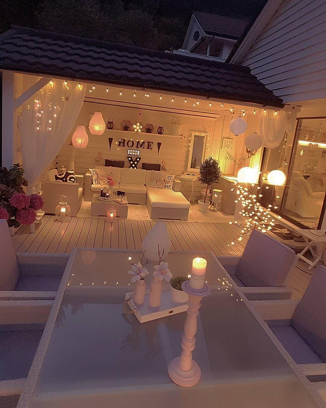 Stanza e terrazzo nei toni del bianco illuminati da lanterne, party ...