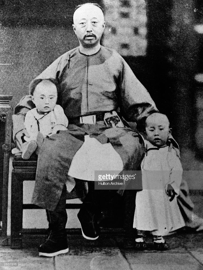 Henry Pu-Yi, (1906 - 1967), last Emperor of China, (1908 - 1912), sitting  on the lap of his father Prince Chun the Regent.