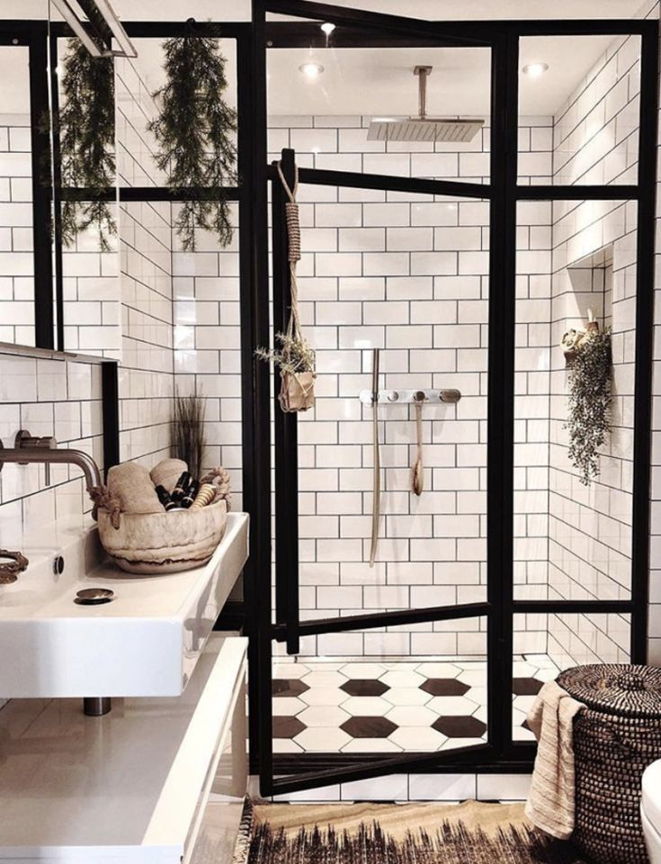 Photo of black and white bathroom with subway tile and black frame around glass shower en…