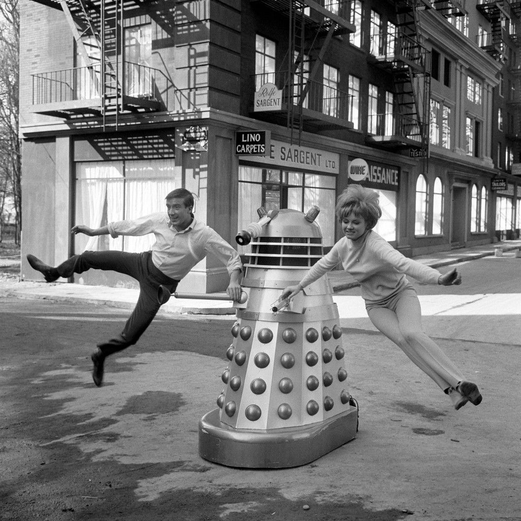 """Swinging on a Dalek at Shepperton Studios are Roy Castle and Jennie Linden, seen practising a dance routine for """"Dr Who and the Daleks. 1965"""