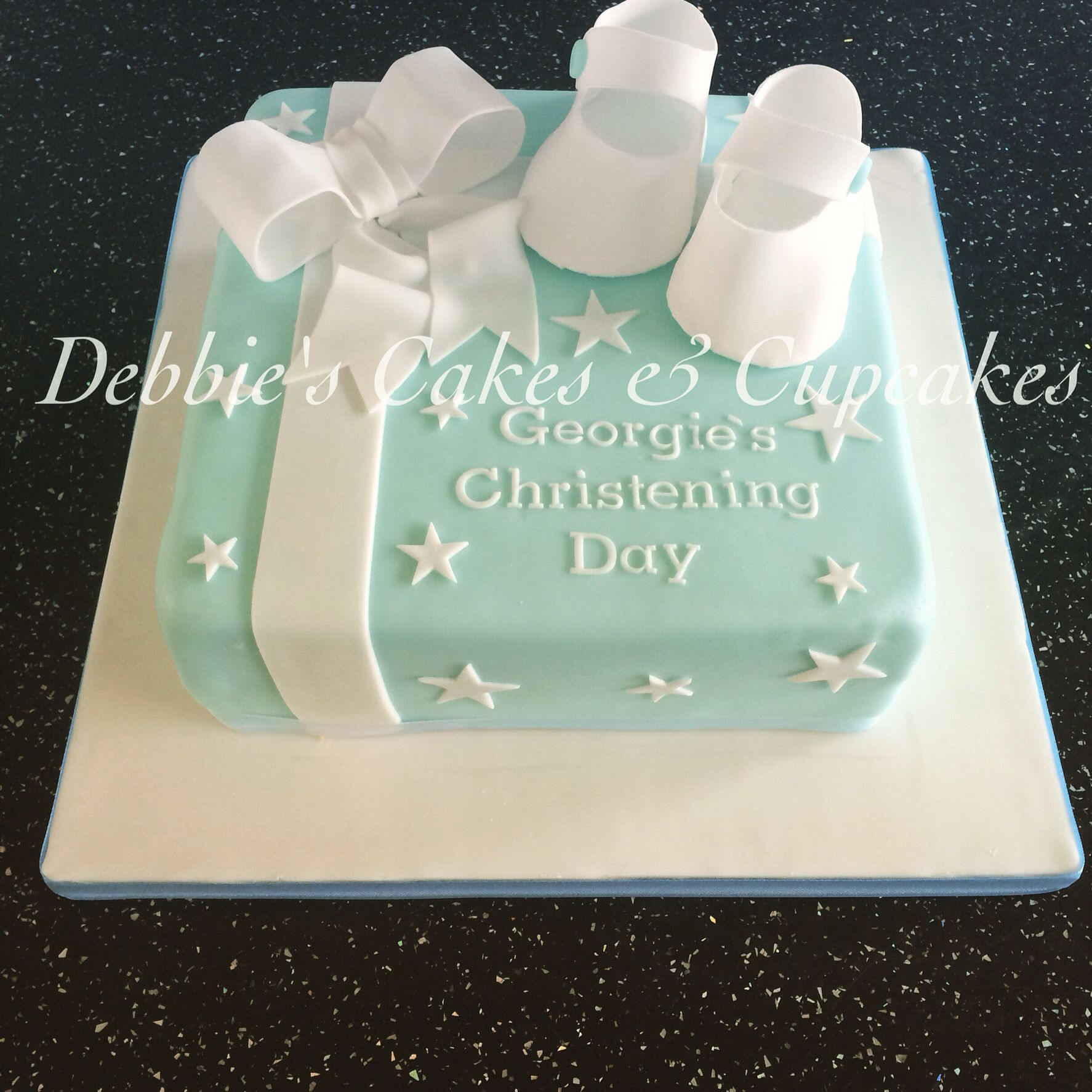 Christening cake for baby boy with booties and bow