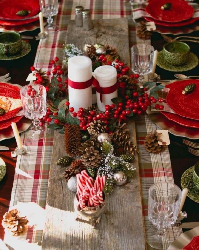 deco table noel rouge et blanc chemin de table a carreaux couronne de feuilles vertes et baies rouges bougies cylindriques blanches et cones de pin