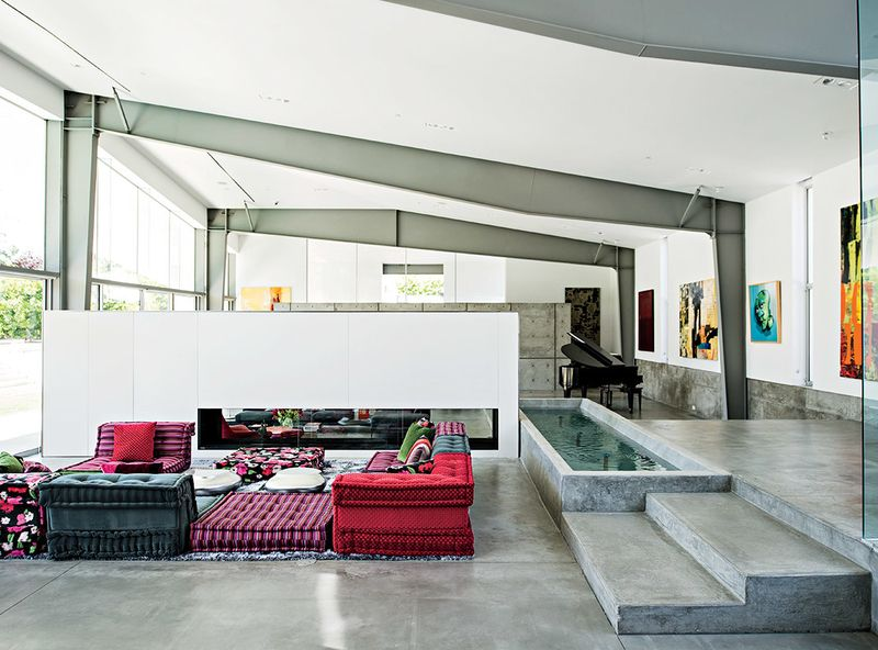 A Mah Jong sofa by Roche Bobois in the living room lends a colorful counterpoint to the custom water feature that runs alongside it.
