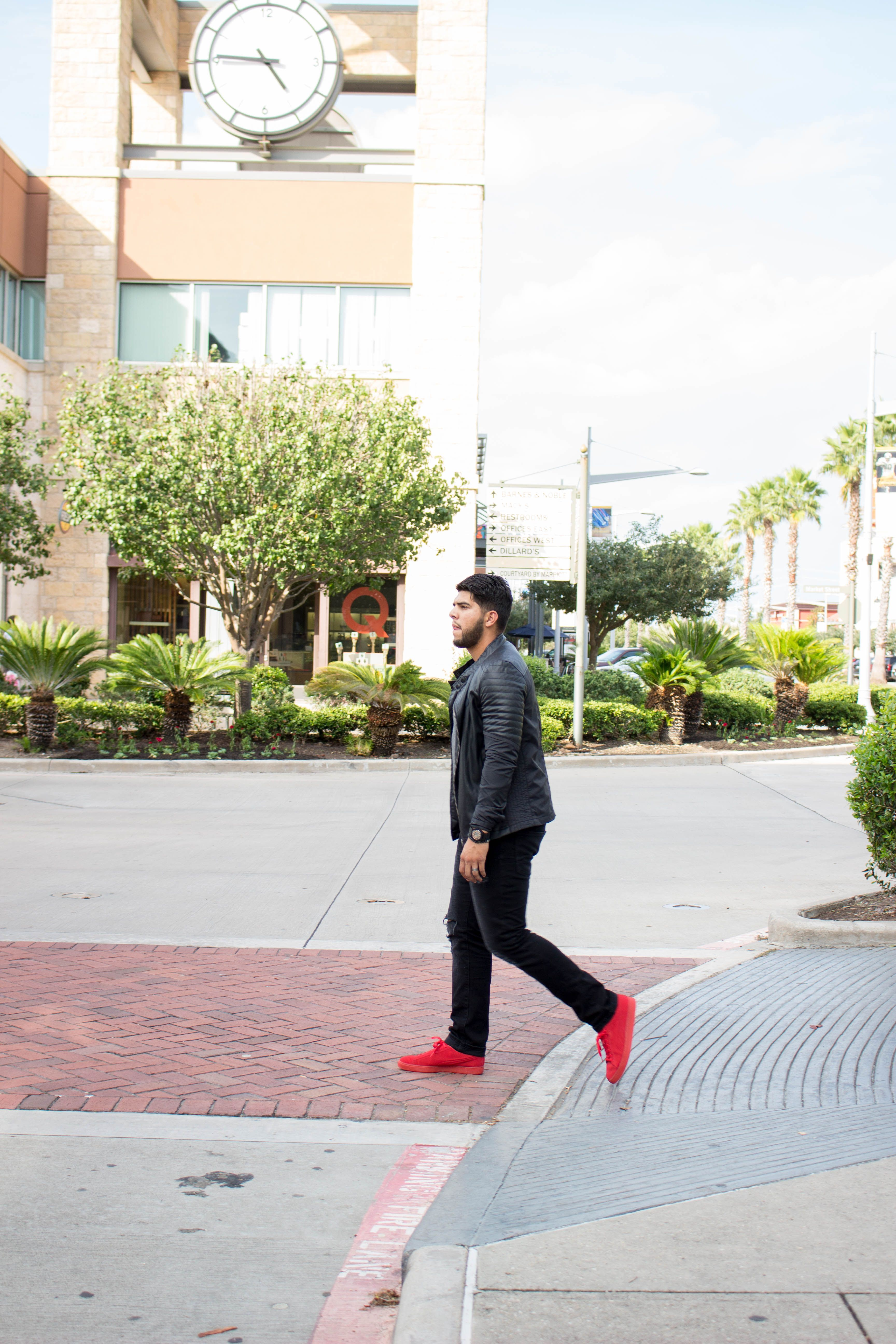 125124a6d All black men's outfit with a pop of color from a pair of red Puma suede  sneakers. Black distressd jeans, and a moto jacket for fall and winter