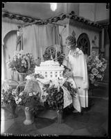 1927-Los Angeles-Aimee Semple McPherson surrounded by flowers, cutting into Angelus Temple cake