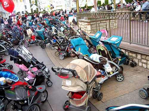 """This is something you will typically see at Disney. A sea of strollers while their owners are in a show or on a ride. We bought a LARGE Mickey balloon to hang from the stroller- kind of like the one you see in the picture. It makes it ALOT easier to spot your stroller in this mess. And alot of times """"crew members"""", as employees are called, will organize the strollers, so yours may not be where you left it!"""
