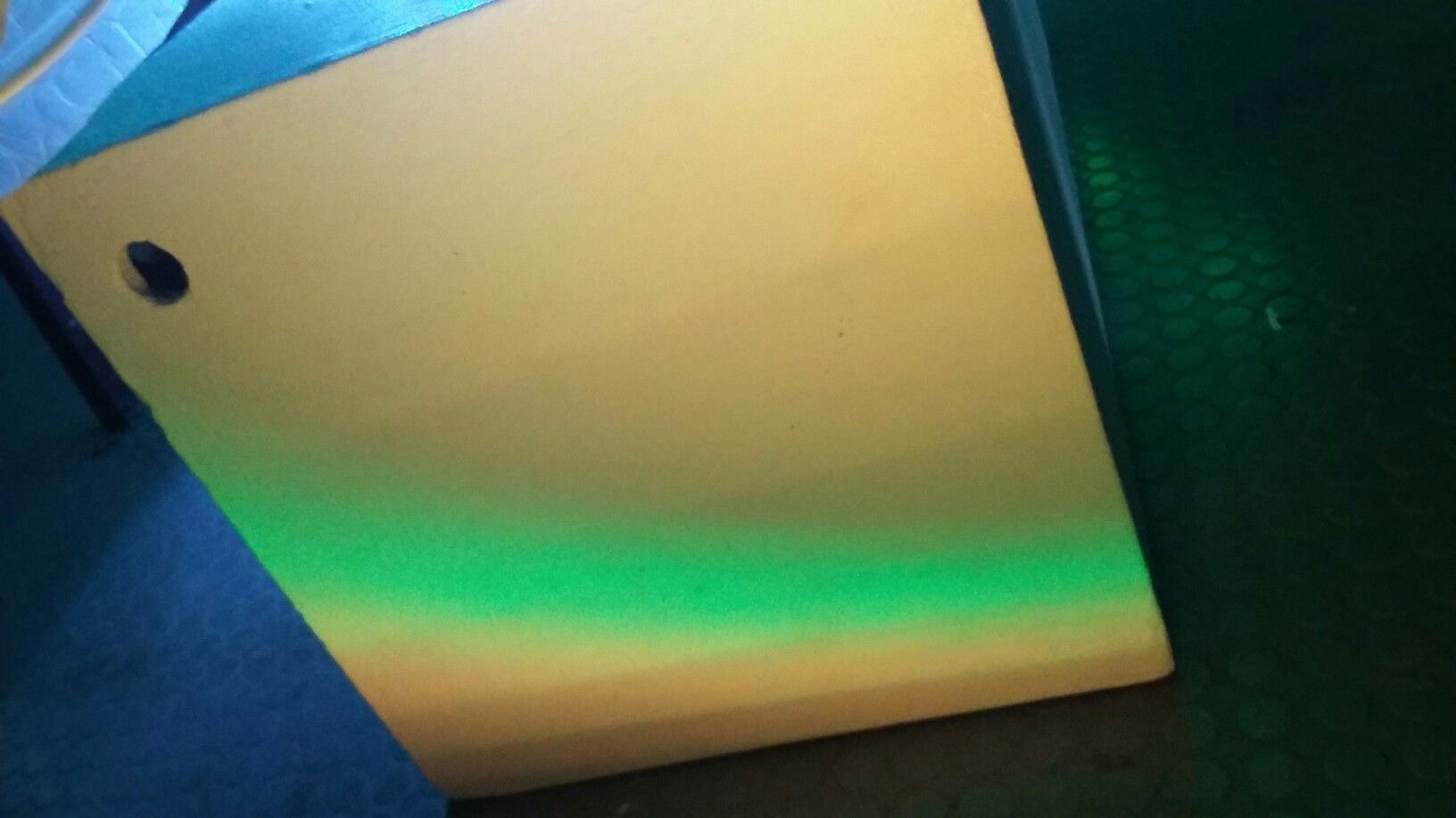 multi coloured light shining onto box - transition of yellow/orange to green