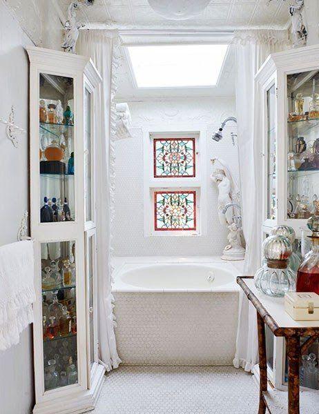Stained glass windows illuminate the penny-tile-sheathed master bath