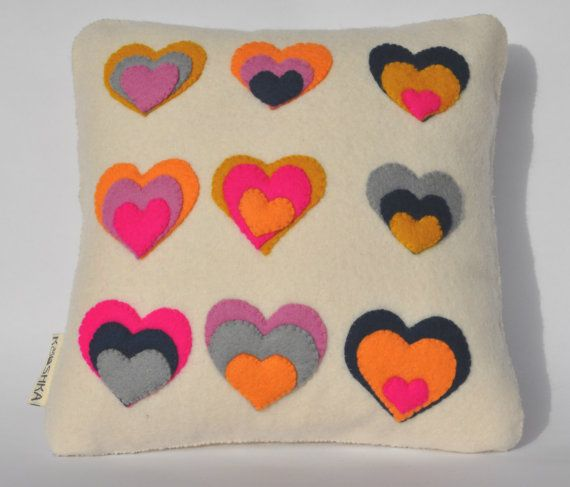 http://www.etsy.com/shop/KOOSHKA 'Cherish all your happy moments; they make a fine cushion for old age'.  Booth Tarkington    Treat a loved one or even yourself to one of these mini 'Pop Heart' cushions made of bright 1.5mm wool felt.     The whole cushion is hand stitched (zip has been machine stitched) with triple layered hearts on front and single heart on back (Care Bear bum style!) £35
