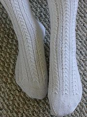 Horseshoe Cable Socks 21 stitches = 2 inches in pattern, stretched. Size 3 needles. 420 yards