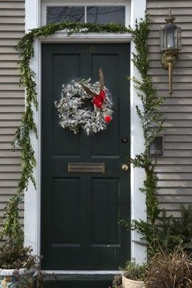 Garland and a wreath adorned with a red-nosed reindeer decorate a home in Old Town Alexandria
