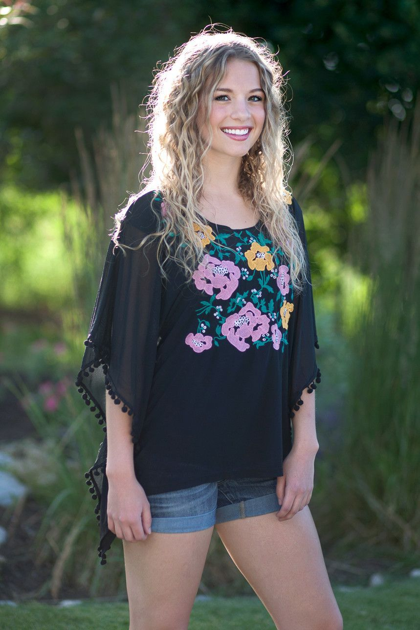 Pom-Pom Poncho Sheer Blouse | Sophia Kaye Does it get any cuter than this? We don't think so! Go casual in jeans or shorts, or dress it up with a skirt or dress pants. Features fabulous pom-poms and beautiful floral stitching.