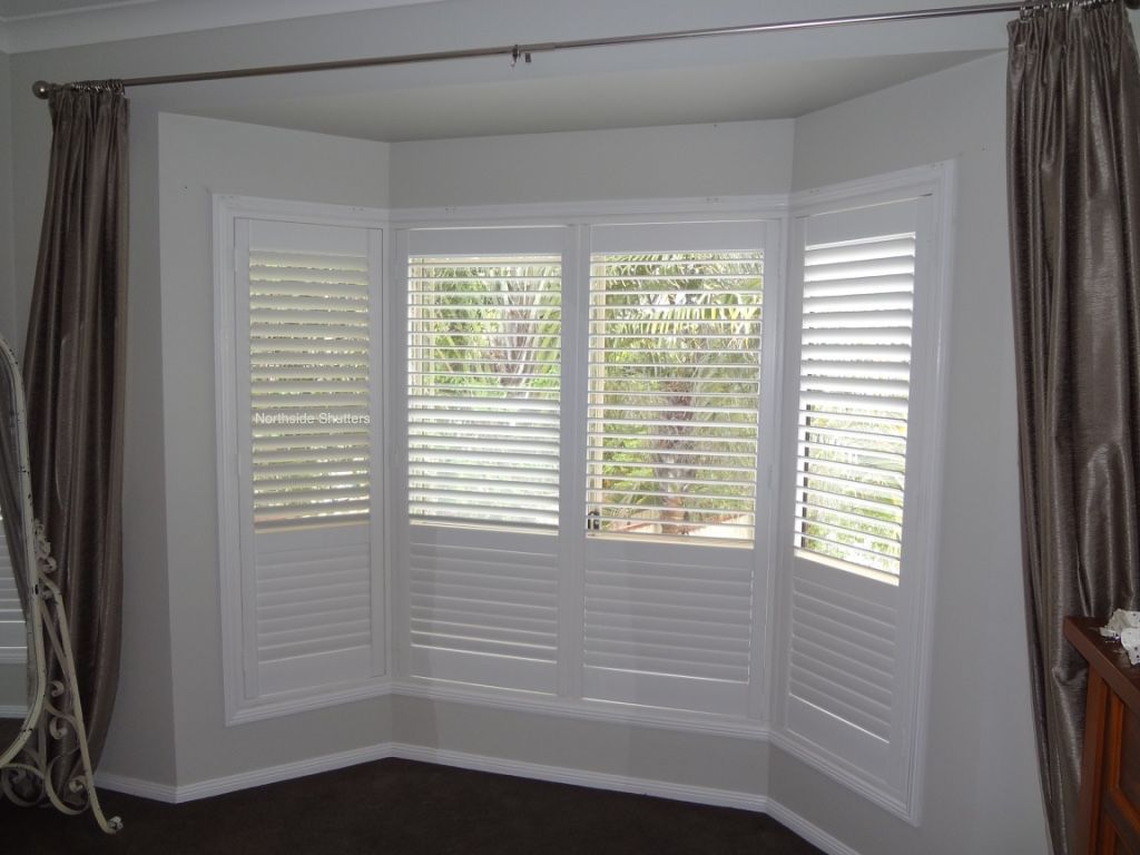 Bay window with PVC plastic plantation shutters 64 mm small blade
