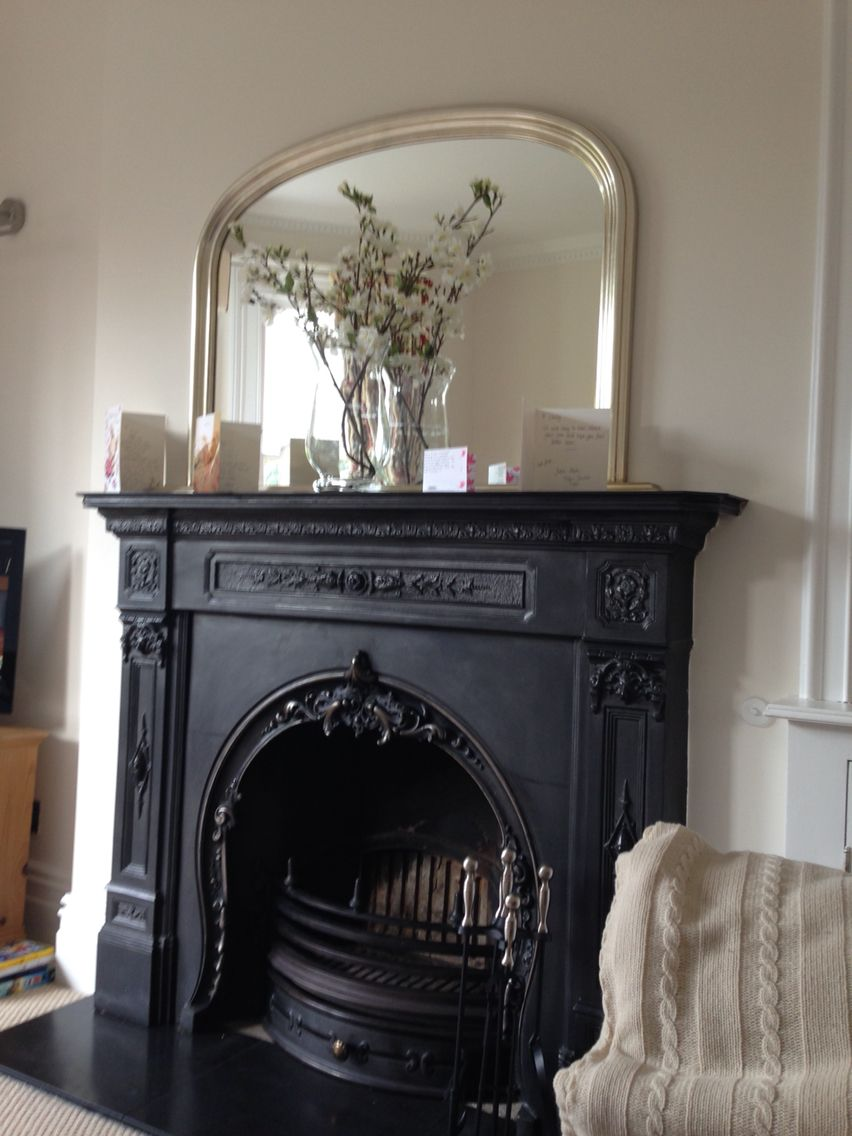 Beautiful iron fireplace with over mantle mirror above hallway and